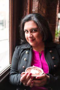 Head shot of author Nisha Sharma holding a cup of cappucino