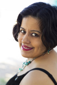 Head shot of author Suleikha Snyder looking over her shoulder at the camera