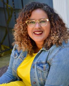 Headshot of Adriana Herrera wearing a yellow shirt and a denim jacket